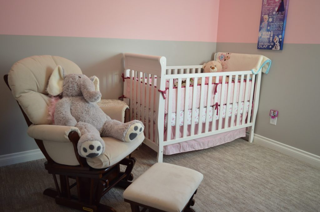 White cot in nursery with teddy on rocking chair