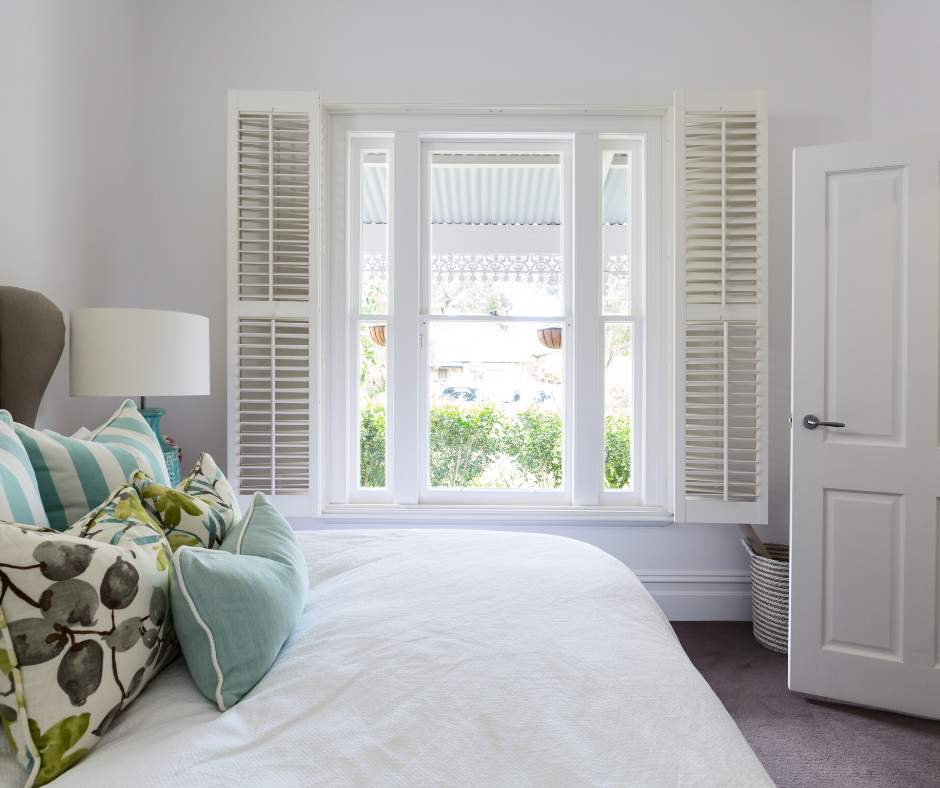 Double Bed in white bedroom with white window and louvres.